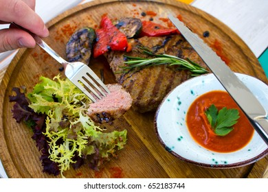 Closeup of sliced grilled steak on  fork in men's hand with sauce on wooden plate