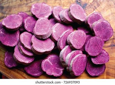 Closeup of sliced Molokai purple sweet potato (Ipomoea batatas) on a wood background.