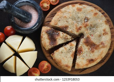 Close-up of sliced ossetian pie, suluguni cheese and tomatoes, view from above