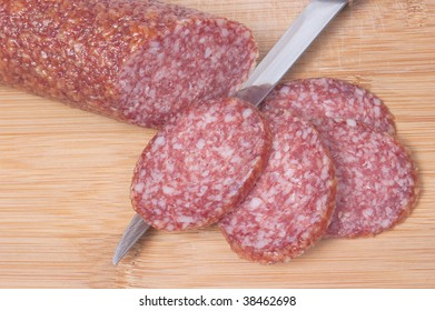 Closeup of sliced salami on cutting board