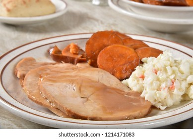 Closeup of sliced turkey breast and gravy with candied yams