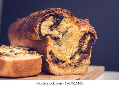 """Closeup of slices of homemade traditional Romanian sweet bread named """"cozonac"""", with cacao, raisins, various nuts and chocolate chips, ready to be eaten."""