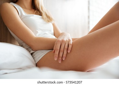 Closeup of slim attractive young woman lying on bed in bedroom