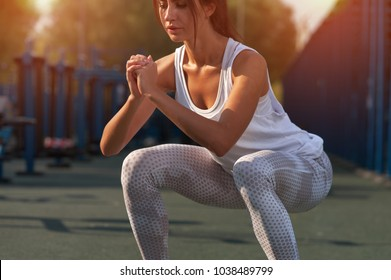 Close-up - Slim brunette woman working out in outdoor gym at summer warm day.