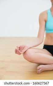 Close-up of a slim cropped woman in lotus pose at fitness studio