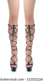 Close-up of slim woman legs standing on white background wearing black platform heel gladiator sandals