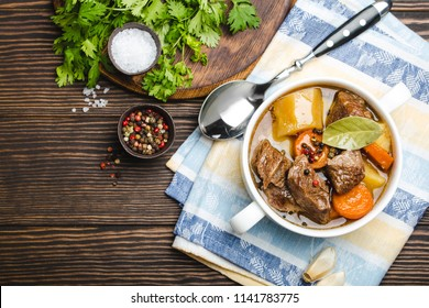 Close-up of slow cooked meat stew ragout in bowl with beef, potato, carrot, broth on wooden rustic background, top view with space for text. Hot homemade food for dinner, meat casserole copy space
