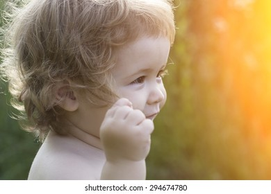 Closeup of small beautiful playful baby boy with blonde curly hair smiling sunny day outdoor on natural background, horizontal picture