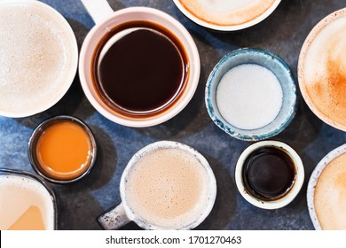 Closeup small and big colorful clay cups with latte, cappuccino, americano, espresso, mocha on grey table in cafe, restaurant. Aromatic morning coffee for breakfast. Hot drinks, beverages concept.