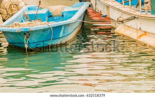 Closeup of small blue fishing boat floating in water tied to a larger white fishing boat.