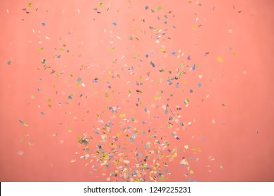 close-up of small confetti falling down in a whirl, flying in mid air. shot in studio, on pink backdrop.