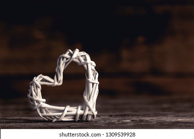 Closeup of small decorative heart made of white wicker composed on wood