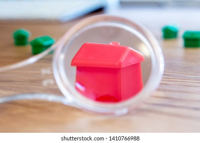 closeup of small house using a magnifier, loupe as a buying new dreamy perfect house for me