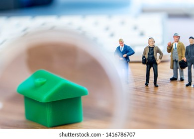 closeup of small house using a magnifier, loupe as a buying new dreamy perfect house for me with small figurines in the background
