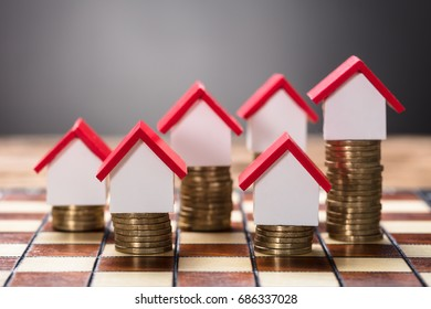 Closeup of small houses on stacked coins on chessboard