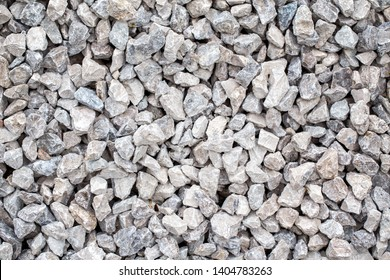 Closeup of small little grey beige blue broken crushed stones rocks lying on ground. Natural environmental background texture. Garden rubble macadam top overhead view.