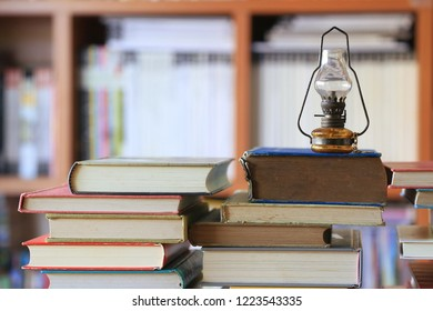 Close Up Of A Small Old Lamp On Library Stack Bookshelf Is The Background