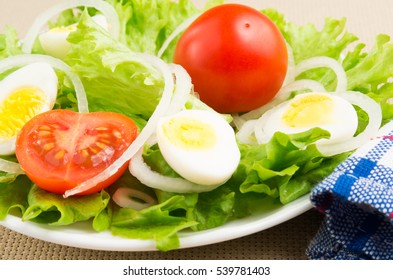 Close-up of a small portion of fresh dishes from the cherry, lettuce, onions and quail eggs