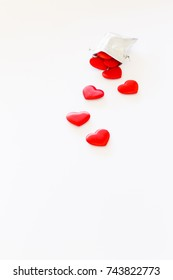 Close-up of a small shiny silver bag filled with cute red velvet hearts on white background. Concept of a romantic love gift for couples, valentines day, marriages or birthdays.