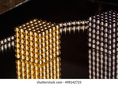 Closeup of small spherical neodymium magnets arranged in cube shapes