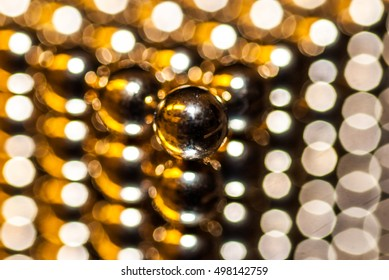 Closeup of small spherical neodymium magnets arranged in a cube shape