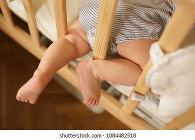 Closeup of small sweet baby legs of child lying on belly in wooden baby cot