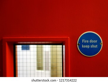 Closeup small warning sign, Fire door keep shut. Selective focus on blue metal badge sign on right side of frame. Space to add text on red surface, blurry mesh grass & white door in backgound.