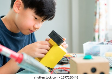 Closeup: Smart looking Asian boy working with circuits, wires, computer chip, OLED, motor, wheels on his robotics project. Science, Technology, Engineering and Mathematics (STEM) education concept.