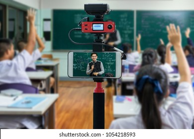 Closeup smart mobile phone taking Live of Asian teacher Giving Lesson over the physics formular in thai laguage on black board in school classroom, technology live streaming and broadcast concept
