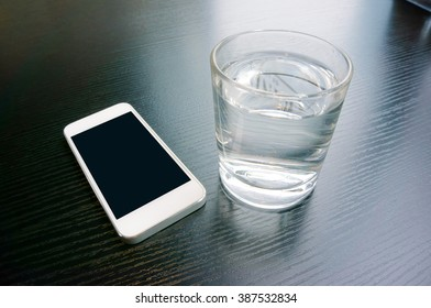 Close-up of a smart phone and a glass of water on a desk.