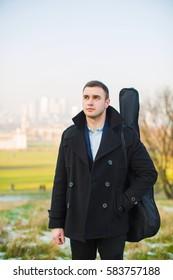Closeup of smart young man hold box guitar outdoor