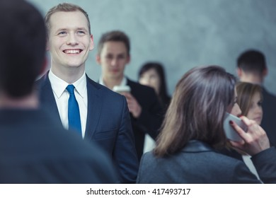 Close-up of a smartly-dressed, cheerful young man in the crowded place