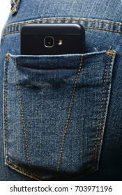 Close-up of a smartphone with a camera in the back pocket of blue jeans.