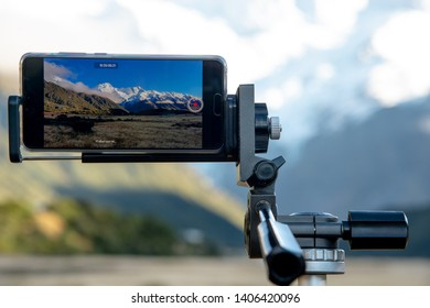 Closeup smartphone camera on tripod capturing a remarkable most popular landscape of Aoraki Mount Cook covered with snow on the peak and clear blue sky  in Mt.Cook National Park , South New Zealand.