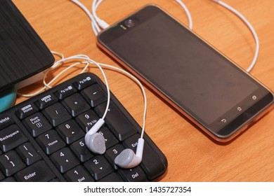 closeup smartphone, earphone with keyboard on the table