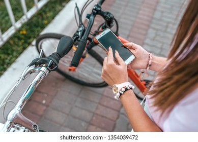 Close-up smartphone girl's hands. In summer city background parking for bicycles, girl chooses route in application, Internet online map on phone. The route of bike path. Bicycle parking city.