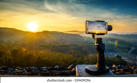 Close-up Smartphone take a Mountians Landscape photo and video timelapse on stand  Mobile Stabilizer in sunset