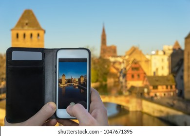 Close-up of a smartphone used to take a picture of the cityscape of Strasbourg with the cathedral Our Lady, Strasbourg, France.