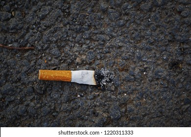 closeup of smashed cigarette butt on asphalt with copy space