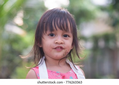 Closeup smiley face of cute asian little girl in the green garden, her face cover with the water colors from playing by painting, concept of learning activity for happy kid lifestyle.