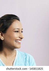 Closeup of smiling Asian woman looking away isolated on colored background