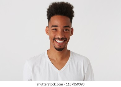 Closeup of smiling attractive african american young man with afro hairstyle wears t shirt feels happy and looks confident isolated over white background