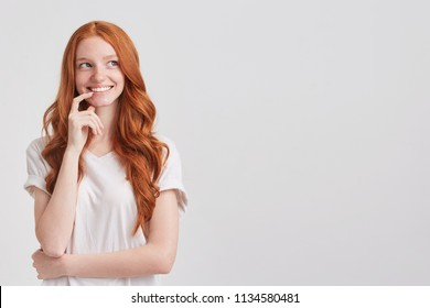 Closeup of smiling beautiful redhead young woman with long wavy hair and freckles wears stylish t shirt keeps hands folded, thinking and looks inspired isolated over white background
