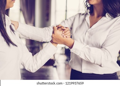 Closeup of smiling business woman supporting colleague in cafe. They are clasping hands and standing with blurred windows in background. Support concept. Side view.