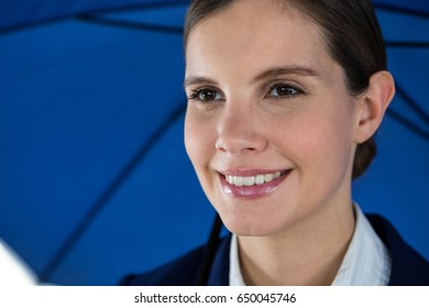 Close-up of smiling businesswoman holding blue umbrella against white background