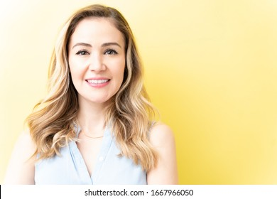 Closeup of smiling Caucasian woman with blond hair against yellow background