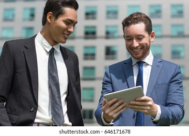 Closeup of Smiling Colleagues Using Tablet Outside