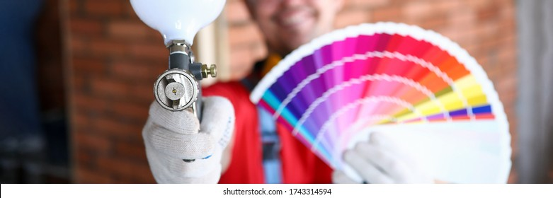 Close-up of smiling construction site worker holding colourful palette with samples and empty professional airbrush gun. Renovation and interior design concept