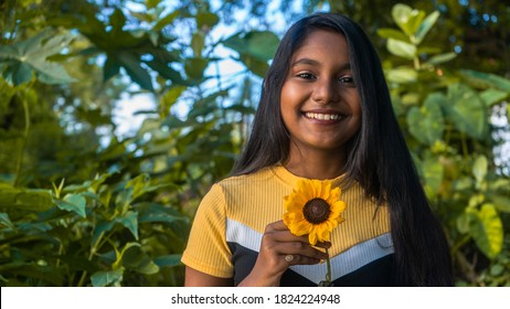 Close-up of a smiling dark-skinned young girl wearing a yellow top. Holding a yellow sunflower at greenery outdoor. Looking at the camera with a cheerful smile.