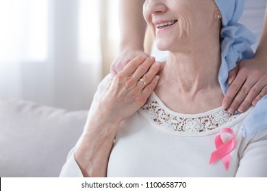 Close-up of smiling elderly woman with pink ribbon as symbol of fight against breast cancer